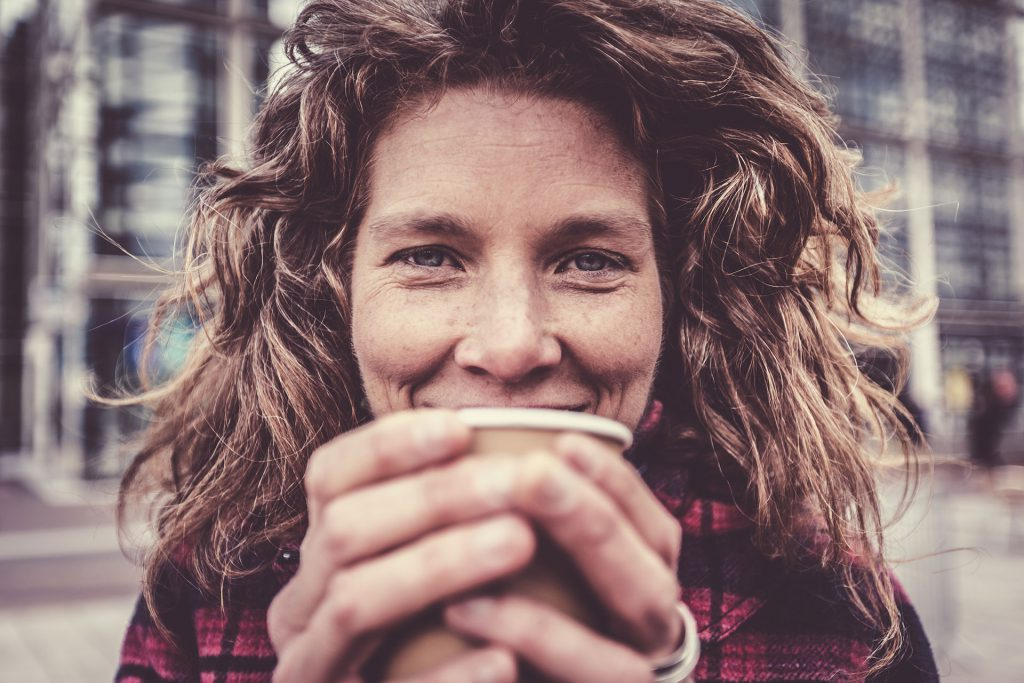 A woman holds a cup in front of her face while smile - we have used an istock photo to protect Emma's identity