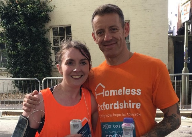 Amber and Chris stand smiling after finishing the Oxford Half. Both are wearing their orange Homeless Oxfordshire t-shirts