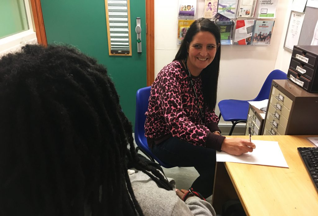 The photo is taken over Penny's shoulder and shows support worker, Sue laughing with her. Penny has black dreadlocks and is wearing a grey top. Sue is wearing a pink leopard pink jumper with her Staff lanyard on.