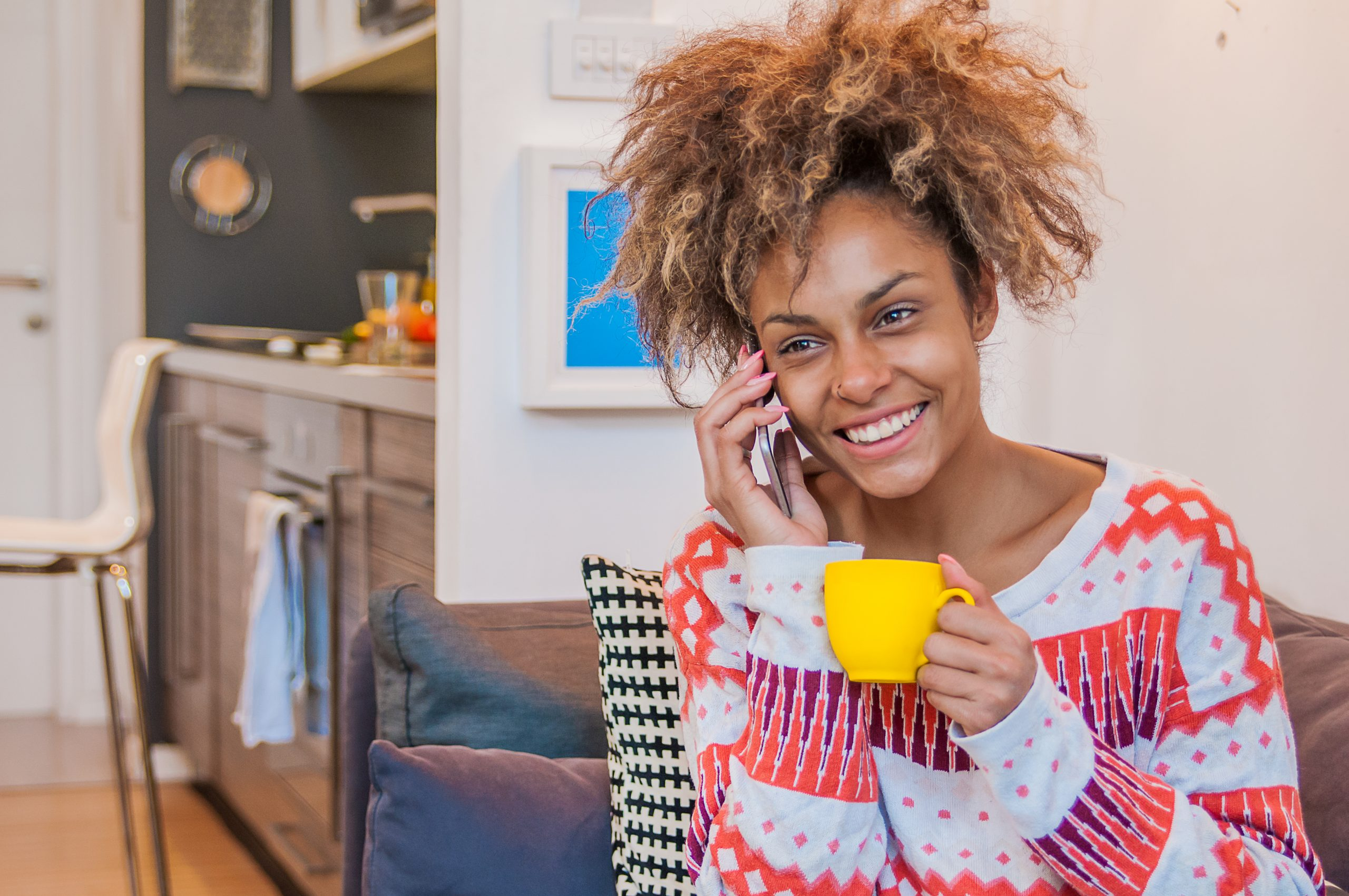 A mixed race woman holding a coffee cup and talking on the mobile phone with smile while sitting on the couch