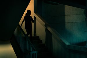 Silhouette of a woman walking down some steps to leave a building