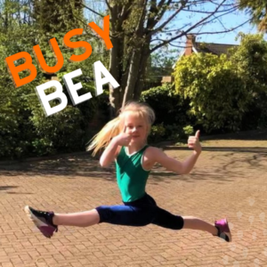 A ten-year old blonde girl with hair in a ponytail jumping mid air with the words 'Busy Bea' written by it